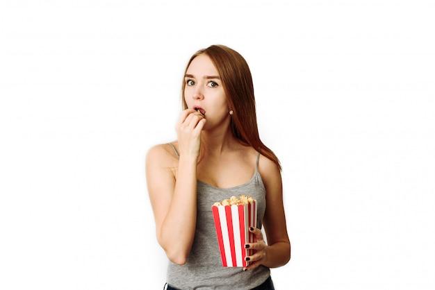 Zainteresowana dziewczyna ogląda film i je popcorn na bielu. kobieta bardzo uważnie patrzy w kamerę