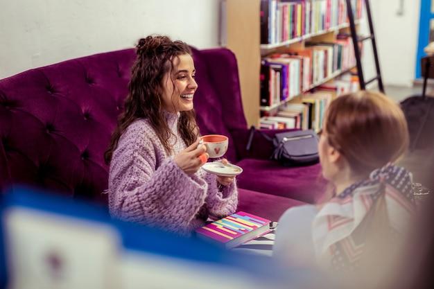 Zainteresowana dziewczyna. śmiejące się dziewczyny siedzące na fioletowej aksamitnej kanapie otoczonej książkami i półkami w niezwykłej kawiarni
