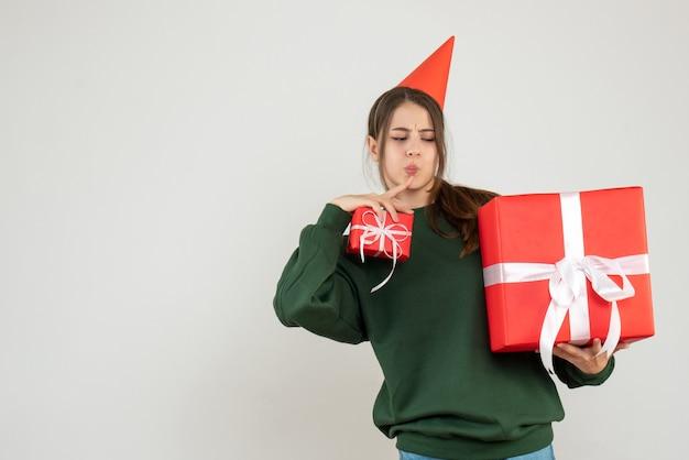 Zainteresowana dziewczyna z czapką strony patrząc na jej prezenty świąteczne na białym tle