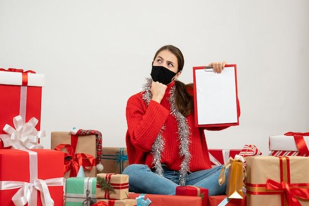 Zainteresowana dziewczyna z czarną maską trzymając dokumenty siedząc wokół przedstawia na białym tle