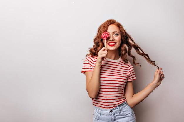 Zainteresowana kaukaska dziewczyna lizanie cukierków z uśmiechem. imbirowa kobieta z czerwonym lizakiem.
