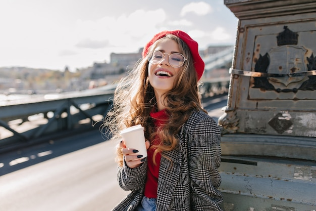 Zainteresowana kaukaska dziewczyna w stroju vintage pijąca kawę podczas podróży po europie
