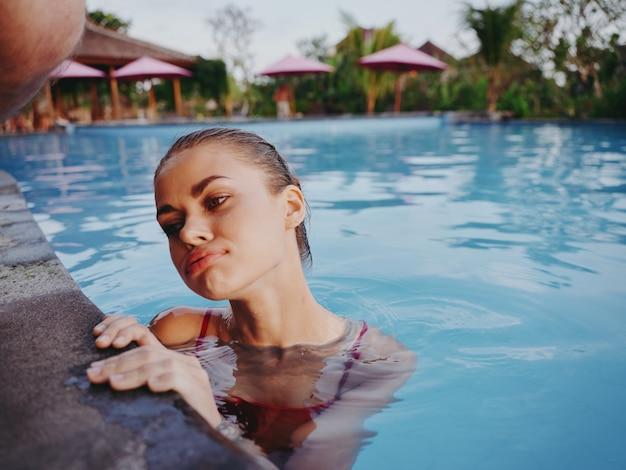 Zainteresowana kobieta oparła się o kafelki basenu i odprężyła urlopowy krajobraz czystej wody