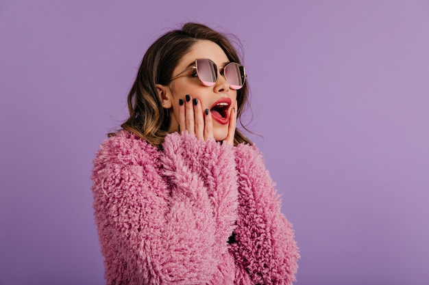 Zainteresowana kobieta pozuje w okularach przeciwsłonecznych