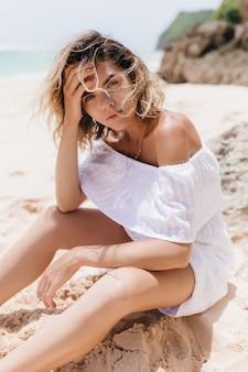 Zainteresowana kobieta w białej sukni siedzi na piasku. niesamowita modelka z krótkimi blond włosami, pozowanie na plaży.