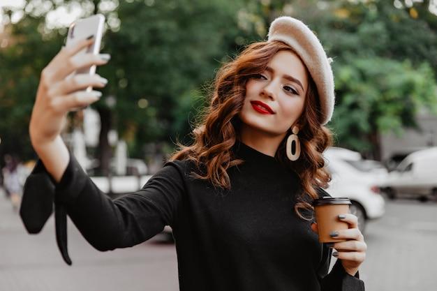 Zainteresowana kobieta we francuskim berecie pozuje w listopadowy poranek. odkryty strzał czarującego modelu imbiru z filiżanką kawy.