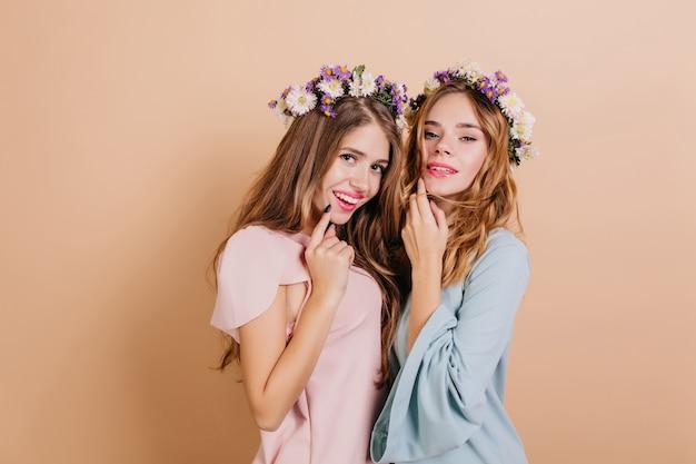 Zainteresowana kobieta z biało-fioletowymi kwiatami we włosach pozuje z siostrą
