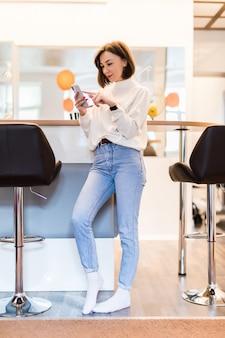 Zainteresowana kobieta z telefonem stoi w panoramicznej kuchni w ubranie