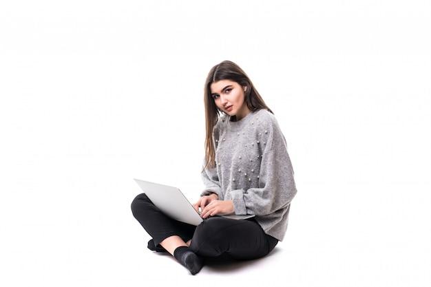 Zainteresowana modelka brunetka w szarym swetrze siedzi na podłodze i pracuje nad swoim laptopem