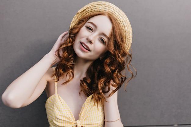 Zainteresowana modna ruda pani pozuje na szarej ścianie w letni dzień. atrakcyjna blada kobieta z kręconymi rudymi włosami dotyka jej kapelusza.