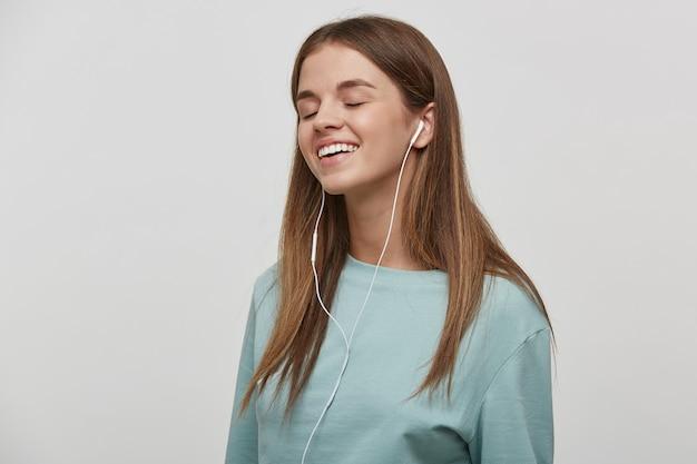 Zainteresowana muzyką młoda kobieta, uśmiecha się, słucha ulubionej muzyki przez słuchawki