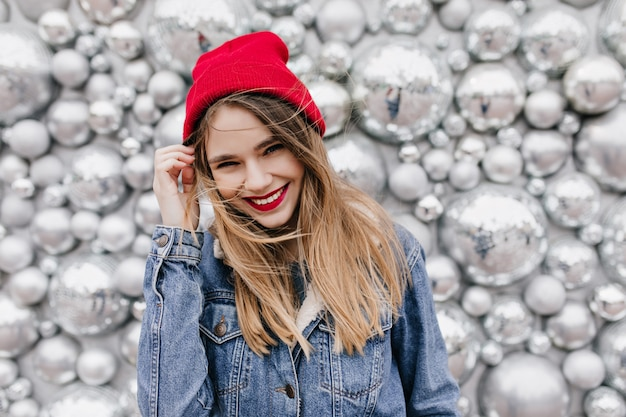 Zainteresowana piękna dziewczyna w dżinsowej kurtce dotykająca jej długich włosów. uśmiechnięta europejska modelka w kapeluszu, pozowanie na błyszczącej ścianie.