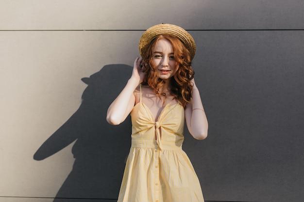 Zainteresowana rudowłosa modelka dotykająca swojego słomkowego letniego kapelusza podczas sesji zdjęciowej. zdjęcie atrakcyjnej rudowłosej kobiety w żółtej sukience relaks w dobry dzień.