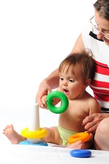 Zainteresowane dziecko zabawą treningową z piramidą. małe dziecko bawiąc się z rodzicem i trzymając pierścień zabawki. portret na odosobnionym białym tle