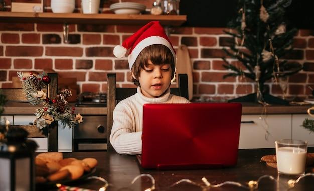 Zainteresowane noworoczne dziecko w białym swetrze i czerwonej noworocznej czapce siedzi przy stole i wpisuje list do czerwonego laptopa