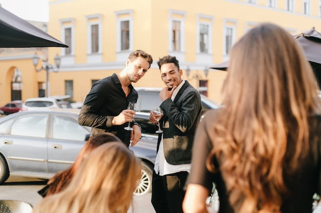 Zainteresowani faceci rozmawiają na ulicy i patrzą na idącą obok blondynkę