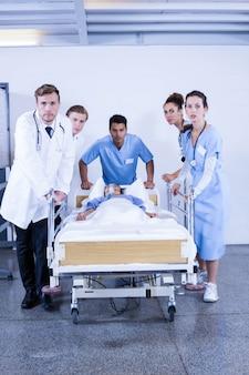 Zainteresowani lekarze stojący w pobliżu pacjenta na łóżku w szpitalu