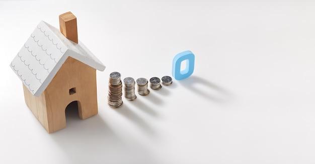 Zainteresowanie planami oszczędzania domu. model domu i stos monet