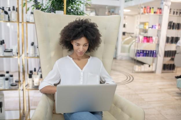 Zainteresowanie, praca. uważny uśmiechnięta młoda kobieta patrząc na laptopa siedząc w fotelu w centrum urody