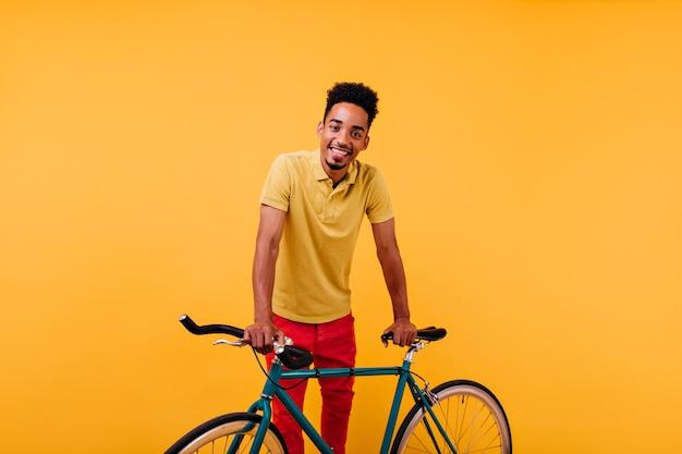 Zainteresowany afrykański model mężczyzna w czerwonych spodniach z uśmiechem. portret inspirowanego czarnego faceta stojącego w pobliżu zielonego roweru.