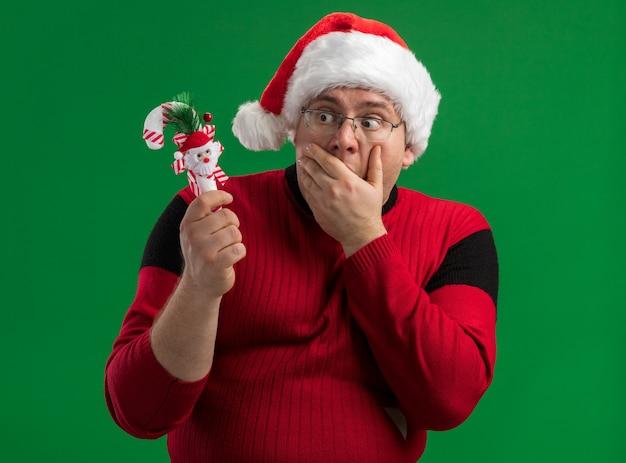 Zainteresowany dorosły mężczyzna w okularach i santa hat trzyma patrząc na ornament z trzciny cukrowej trzymając rękę na ustach na białym tle na zielonym tle