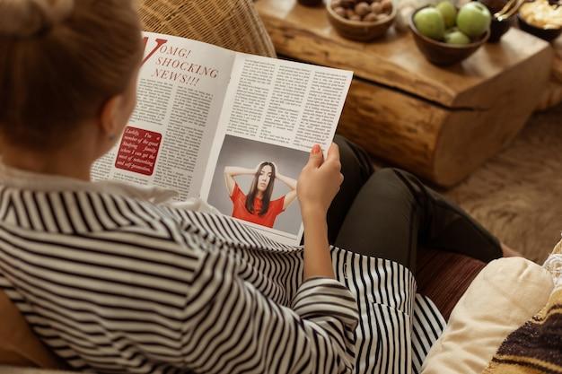 Zainteresowany informacjami. skupiony klient siadający na wygodnej sofie i sprawdzający najnowsze wydanie magazynu o modzie