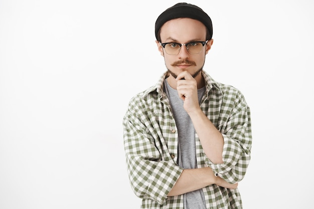Zainteresowany twórczy brodaty młody mężczyzna w czarnej czapce i okularach trzyma rękę na brodzie i patrzy z poważnym zamyślonym wyrazem myśli słucha ciekawy plan