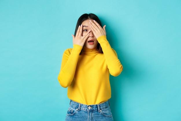 Zaintrygowana azjatka zerkająca przez palce na coś ciekawego, z zaciekawieniem patrząc w kamerę, stojąca na niebieskim tle.