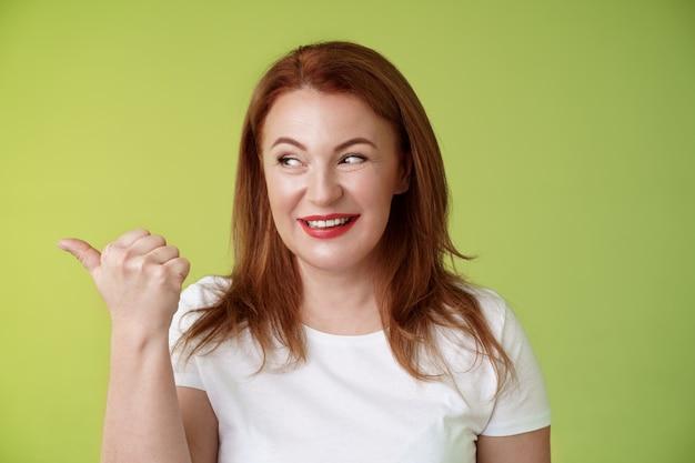 Zaintrygowana, charyzmatyczna rudowłosa kobieta w średnim wieku, uśmiechnięta pokusa z zainteresowaniem, wskazująca z ciekawością w lewo