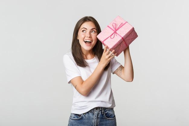 Zaintrygowana dziewczyna z okazji urodzin potrząsa pudełkiem prezentowym, aby dowiedzieć się, co jest w środku.