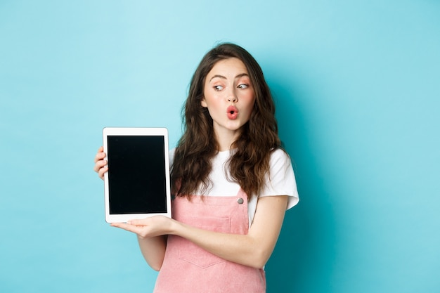 Zaintrygowana glamour dziewczyna patrząca na ekran cyfrowego tabletu, pokazując go tobie, stojąc rozbawiona ofertą promocyjną online, demonstruje coś na wyświetlaczu, niebieskim tle.