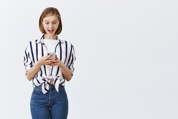 Zaintrygowana i podekscytowana młoda kobieta sprawdza wiadomości lub konto bankowe na telefonie, ze zdumieniem patrzy na smartfona