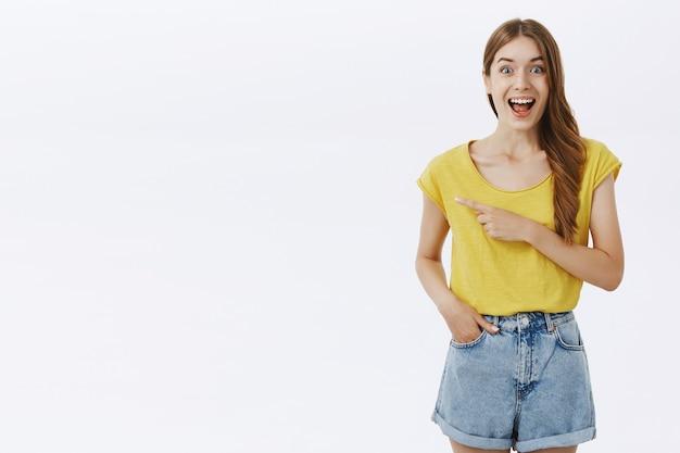 Zaintrygowana ładna dziewczyna wyglądająca na rozbawioną, wskazując palcem w lewo
