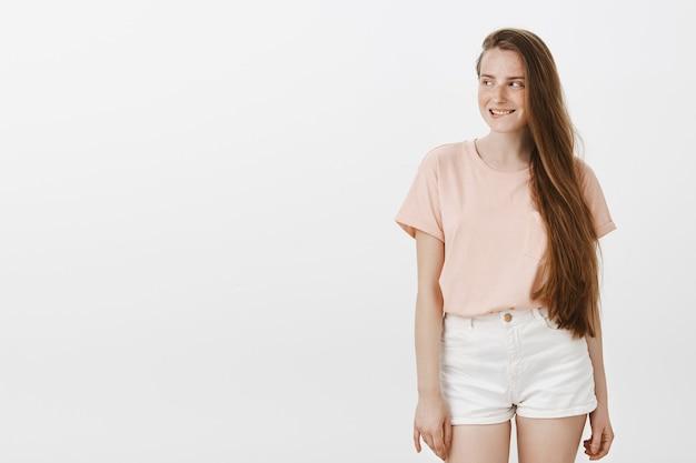 Zaintrygowana ładna nastolatka pozuje pod białą ścianą