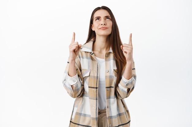 Zaintrygowana młoda kobieta, klientka podejmująca decyzję w sklepie, wskazująca i patrząca w górę zamyślona, wybierająca przedmiot w sklepie, stojąca nad białą ścianą
