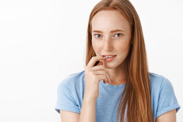Zaintrygowana zalotna i kobieca urocza rudowłosa kobieta z uroczymi piegami trzymająca palec na dolnej wardze, wpatrująca się uwodzicielsko z pożądaniem i zamiarem pocałunku