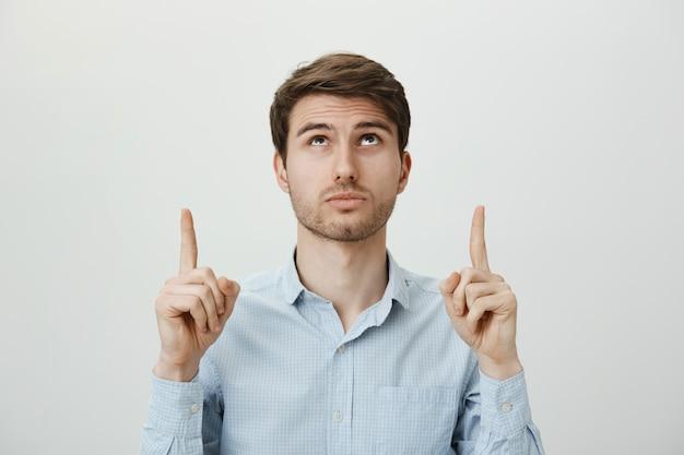 Zaintrygowany brodaty młody mężczyzna patrząc i wskazując na reklamę