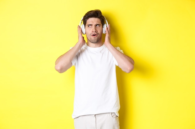 Zaintrygowany facet cieszący się melodiami w słuchawkach, słuchający z bliska muzyki w słuchawkach, stojący nad żółtym tłem.