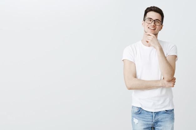 Zaintrygowany inteligentny facet w okularach myśli, zobacz ciekawy wybór