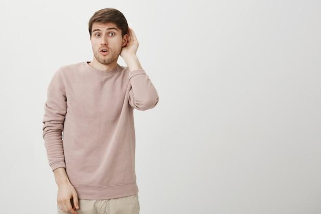 Zaintrygowany uroczy facet podsłuchuje, trzymaj rękę przy uchu