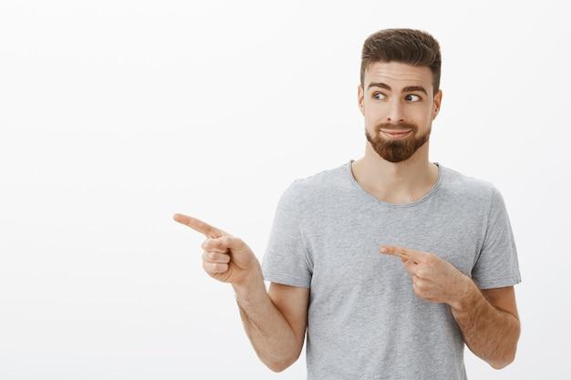 Zaintrygowany, uroczy i przyjazny męski mężczyzna z brodą i brązową fryzurą, wskazujący i patrząc w lewo uśmiechnięty podekscytowany, pokazujący ulubione miejsce do kopiowania, zachwycony i szczęśliwy na szarej ścianie
