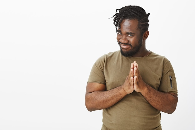 Zaintrygowany zabawny facet w brązowej koszulce pozujący na białej ścianie