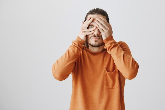Zaintrygowany zabawny facet zamyka oczy i zaciekawiony zerka przez palce