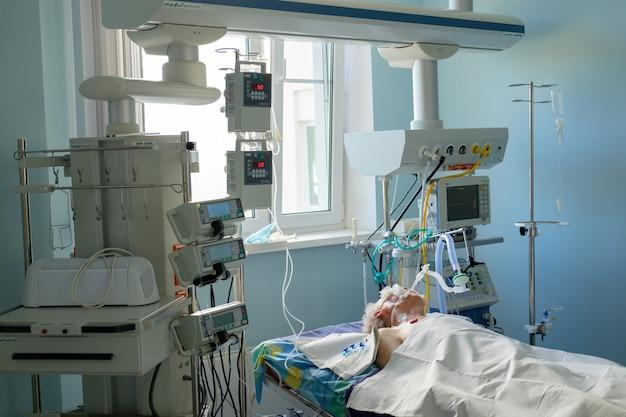 Zaintubowany dorosły biały mężczyzna pod avl leżący w śpiączce na oddziale intensywnej terapii. pacjent w stanie krytycznym.