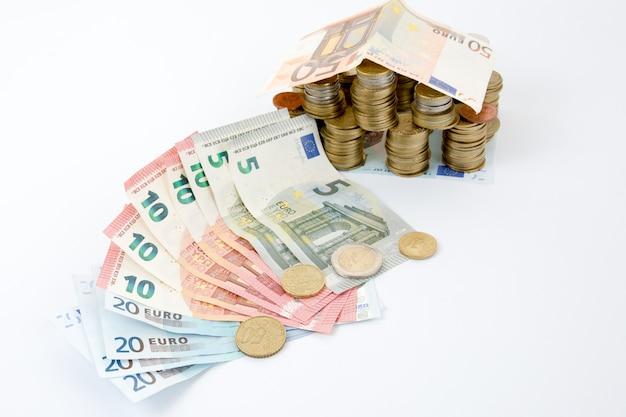 Zainwestuj w koncepcję nieruchomości. rachunku dach na monetach odizolowywać na biel ścianie.