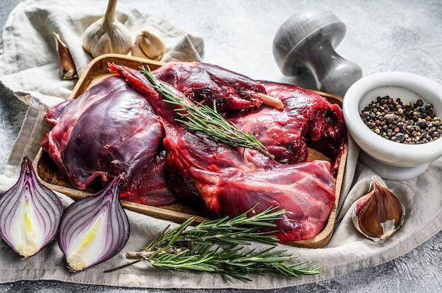 Zające mięso surowa świeża dzika zając na drewnianym stole z warzywami i pikantność. widok z góry. mięso ekologiczne