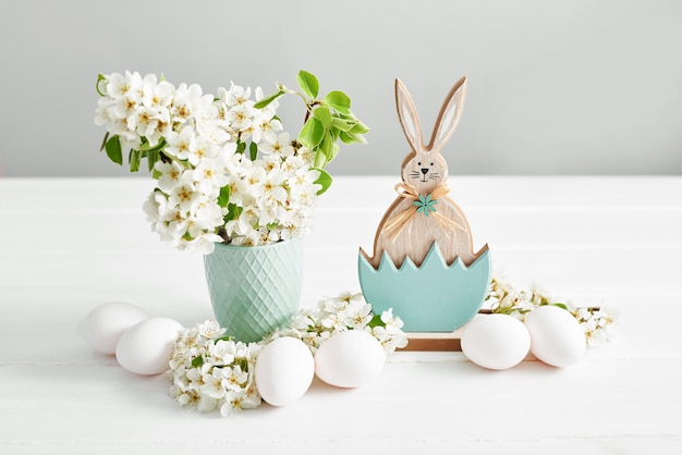 Zajączek i białe pisanki i gałąź wiosna z kwiatami. wiosna wielkanoc kwiaty wiśniowe kwitnienie. wiosenne kwiaty. piękny sad. wiosna
