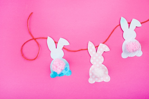Zajączek ozdoba papieru wyciąć tło. ręcznie robiona świąteczna girlanda z kolorowych królików i narzędzi rzemieślniczych.