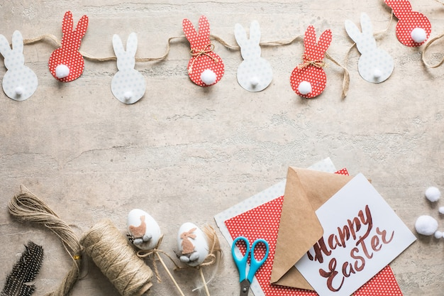 Zajączek ozdoba papieru wyciąć tło. świąteczna girlanda rękodzieła z kolorowych królików i narzędzi rzemieślniczych. widok z góry z miejscem na kopię