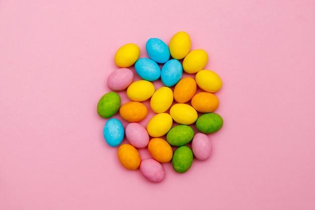 Zajączek wielkanocny. wesołych świąt wielkanocnych koncepcja tło wakacje. płaskie leżał kolorowe jajko króliczek z akcesoriami do świętowania na nowoczesnym rustykalnym różowym papierze do pasteli w domowym biurze.